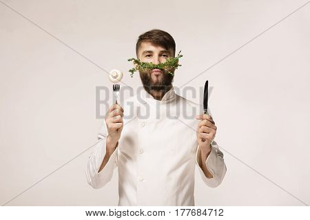 Chef's menu logo. Vegan restaurant logo. Symbol of healthy food. CONCEPT OF HEALTHY FOOD. Handsome funny cheff holding spoon and knife and herbs like a mustache. Professional chef.