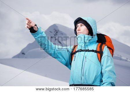 The mountaineer pointing at peak, standing against a winter mountain landscape.