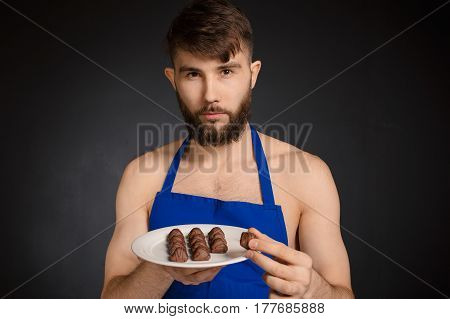 Hot sexy naked handsome man with chocolates chocolate candies. Smiling naked handsome man wearing dark blue apron holding a white plate with many sweets chocolate candies. Handsome confectioner.