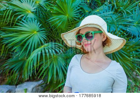 Young girl in the park in green glasses and hat in Mexico