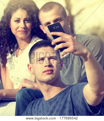 Group of young people having fun taking selfie with smarthphone in park