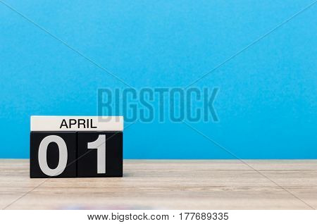 April 1st. Day 1 of month, calendar on wooden table and blue background. Spring time, empty space for text.