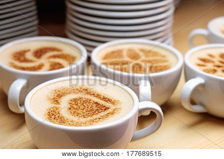 Cup of cappuccino decorated cinnamon. few cups on a wooden table