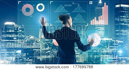 Back view of businesswoman working with virtual panel and night city at background
