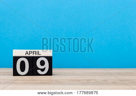April 9th. Day 9 of month, calendar on wooden table and blue background. Spring time, empty space for text.