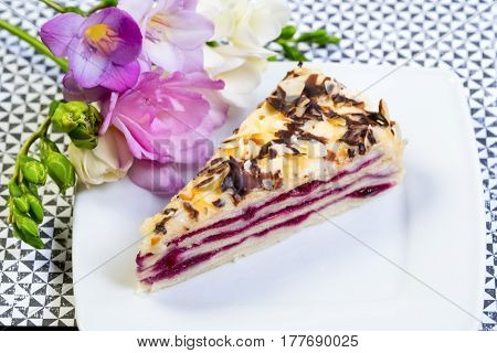 Blueberrycake on white plate and wooden table. Decorated with orchid flower