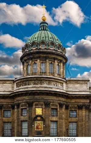 Fragment of the building of the Kazan Cathedral in Saint-Petersburg with a green dome and gold cross against the blue sky with white clouds.