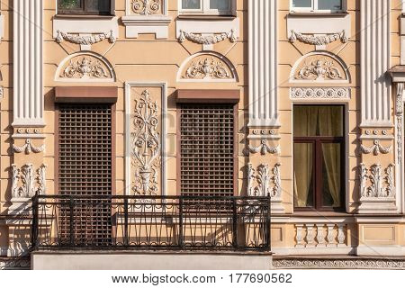 Windows with grilles moldings and a balcony with a metal grating on the facade of the beige building. From the window series Saint-Petersburg.