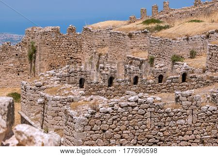 Ruined wall of ancient fortress Acrocorinth against the blue sky on a bright sunny day. Peloponnese Greece.