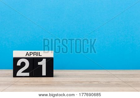 April 21st. Day 21 of month, calendar on wooden table and blue background. Spring time, empty space for text.