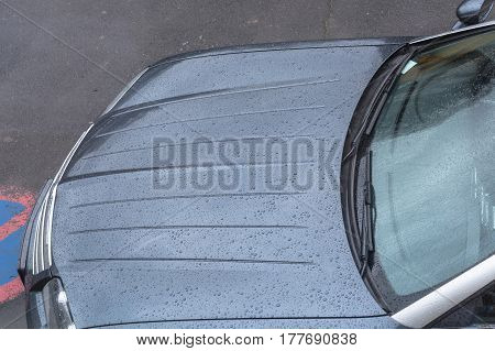 Rolling off water droplets on a car bonnet.