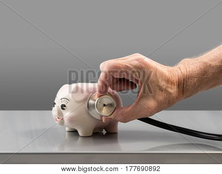 Senior male doctor or vet checking the condition of a small pink piggy bank to illustrate savings or retirement