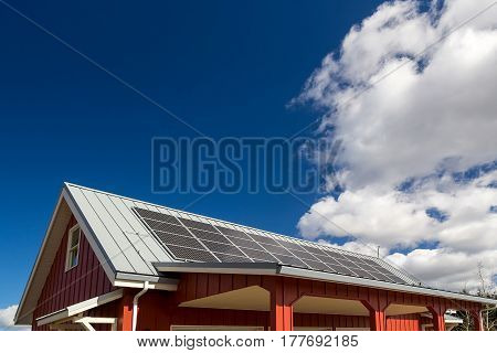 Solar Panels for generating eco-friendly electricity on the rooftop of red house against white clouds and blue sky