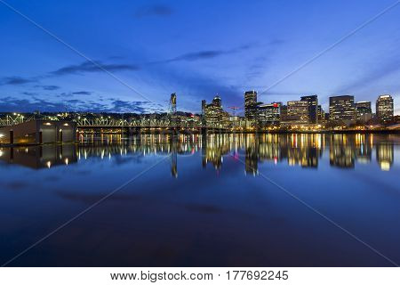 Portland Oregon downtown city skyline by Hawthorne Bridge over Willamette River waterfront during evening blue hour