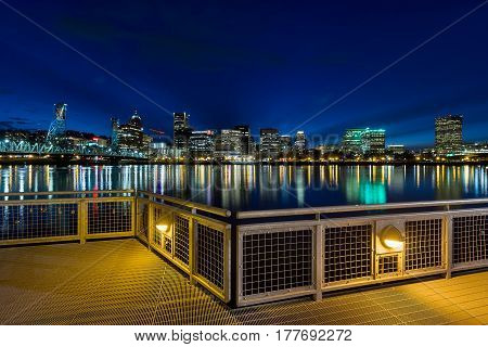 Portland Oregon downtown city skyline from Eastbank Esplanade along Willamette River waterfront during blue hour