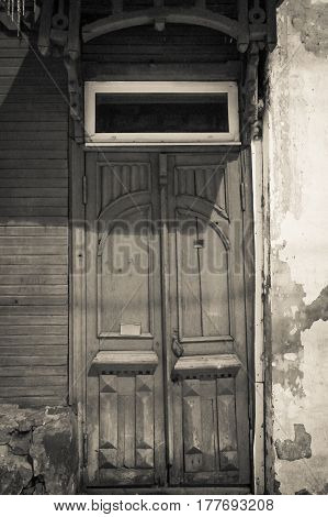The vintage door of the old house is a black and white