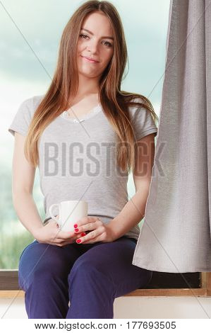 Young Woman Holding Cup Drink Sitting On Windowsill
