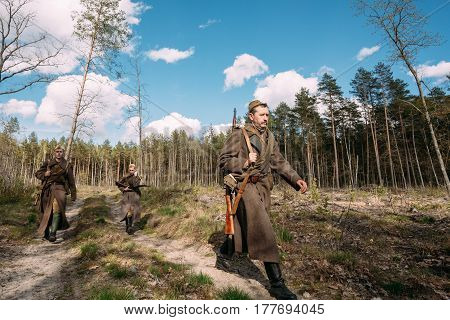 Pribor, Belarus - April 23, 2016: Group Of Re-enactors Dressed As Soviet Russian Red Army Infantry Soldiers Of World War II Marching Along Forest Road At Spring Season.