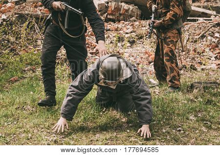 Re-enactors Dressed As Russian Soviet Soldiers Of World War II Performing Mopping-up Operation. German Soldier Come Out Of Ambush And Surrender To Captivity. poster