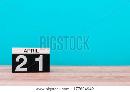 April 21st. Day 21 of month, calendar on wooden table and turquoise background. Spring time, empty space for text.