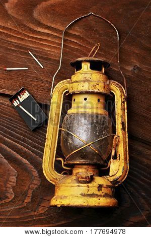 The old kerosene lantern laying with scattered maatches on the wooden table