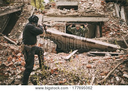 Pribor, Belarus - April 24, 2016: Re-enactor Dressed As Russian Soviet Soldier Of World War II Performing Mopping-up Operation. German Soldier With Raised Hands Come Out And Surrender To Captivity