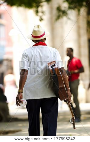 Cuban man wearing traditional panama straw hat playing an acoustic guitar. Taken in Trinidad, Cuba
