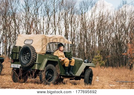 Rogachev, Belarus - February 25, 2017: Re-enactor Dressed As Russian Soviet Red Army Infantry Soldier Of World War II Sitting In Soviet four-wheel drive Army Truck GAZ-67