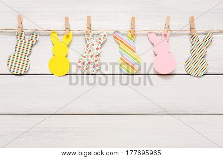 Easter bunny craft paper garland decoration background. DIY holiday handicraft stripe of colorful rabbits. Top view with copy space on white wood