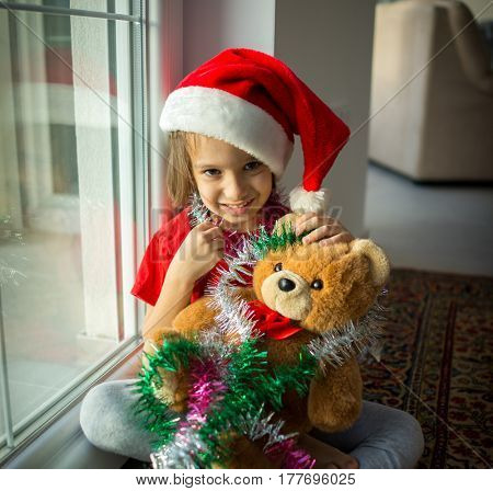 Little cute kid in red cap of Santa Claus celebrates Christmas