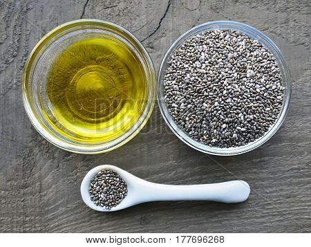 Chia oil with chia seeds in a glass bowls on old wooden background.Organic chia seed oil.Healthy food,superfood or bodycare concept.Selective focus.