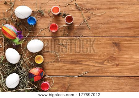 Easter eggs craft copy space background. Paint colorful handmade holiday decoration, preparing for happy event. Top view on rustic wood with spring flowers