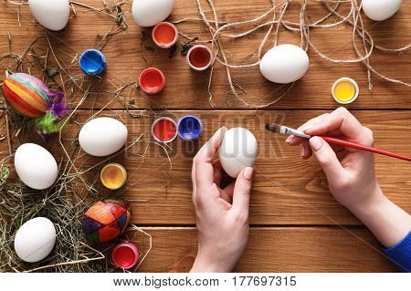 Easter eggs craft. Paint colorful handmade holiday decoration, preparing for happy event. Artist hands draw, top view on rustic wood background