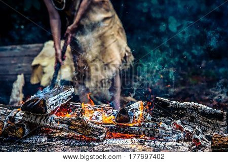A hot bed of coals with a Native American woman in the background.