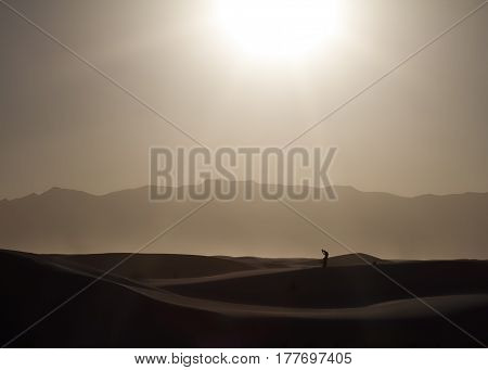The silhouette of a man with kids in the New Mexico desert.