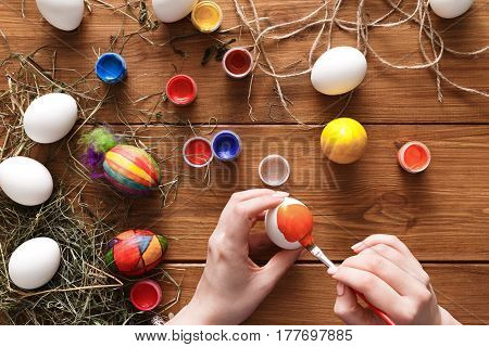 Easter eggs craft. Hands paint colorful handmade holiday decoration, top view on rustic wood background