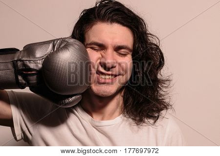 Guy in the boxing glove beats himself in the face. Emotion photo.