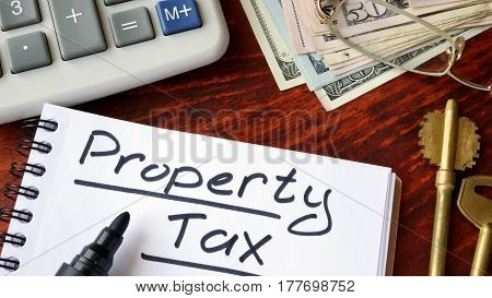 Property tax written in a notebook and calculator.
