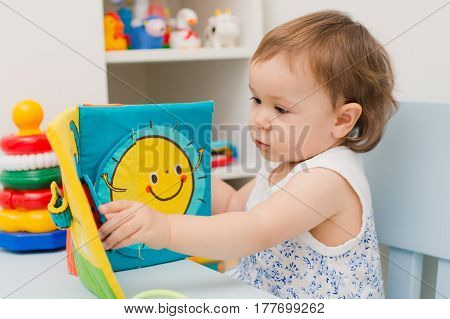 baby girl playing with educational toy nursery