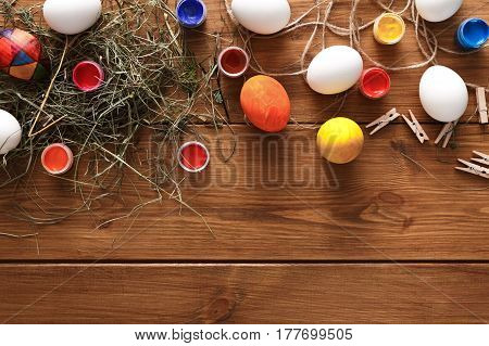 Paint easter eggs, handmade craft background. Top view of making holiday decorations on rustic wood with hay
