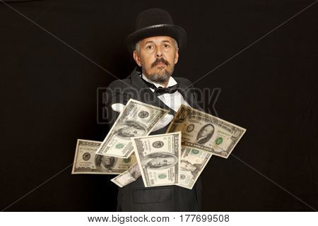 Magician show with dollars banknote. Isolated on black background