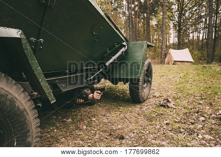 Pribor, Belarus - April 24, 2016: Re-enactor Dressed As Russian Soviet Crew Soldier Of World War II Lying On Ground Under Armoured Soviet Scout Car Ba-64 In Forest And Shooting A Handgun Gun At Enemy