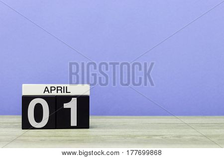 April 1st. Day 1 of month, calendar on wooden table and purple background. Spring time, empty space for text.