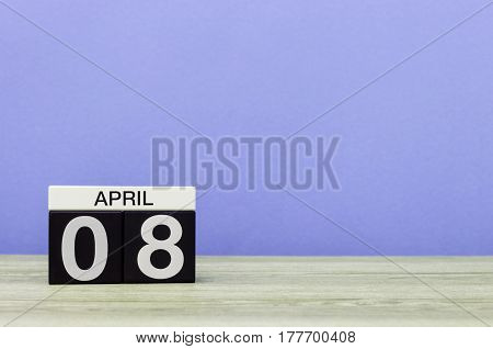 April 8th. Day 8 of month, calendar on wooden table and purple background. Spring time, empty space for text.