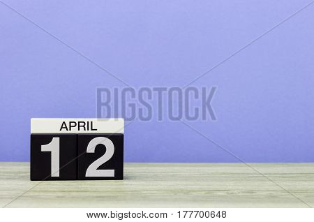 April 12th. Day 12 of month, calendar on wooden table and purple background. Spring time, empty space for text.