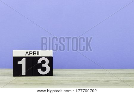 April 13th. Day 13 of month, calendar on wooden table and purple background. Spring time, empty space for text.