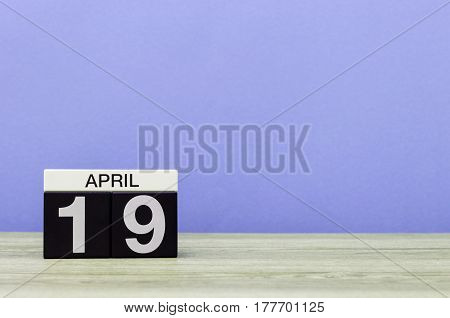 April 19th. Day 19 of month, calendar on wooden table and purple background. Spring time, empty space for text.