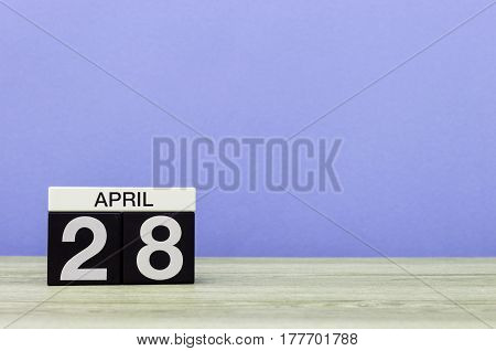 April 28th. Day 28 of month, calendar on wooden table and purple background. Spring time, empty space for text.