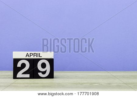 April 29th. Day 29 of month, calendar on wooden table and purple background. Spring time, empty space for text.
