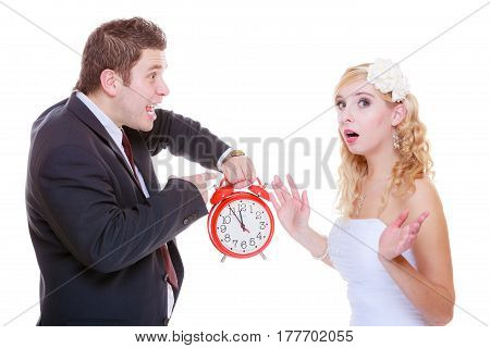 Wedding waiting for celebration and proposal negative bad relationship concept. Groom holding bid red clock yelling at his birde future wife in white dress.